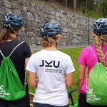 drei Frauen in JKU Kleidung von hinten